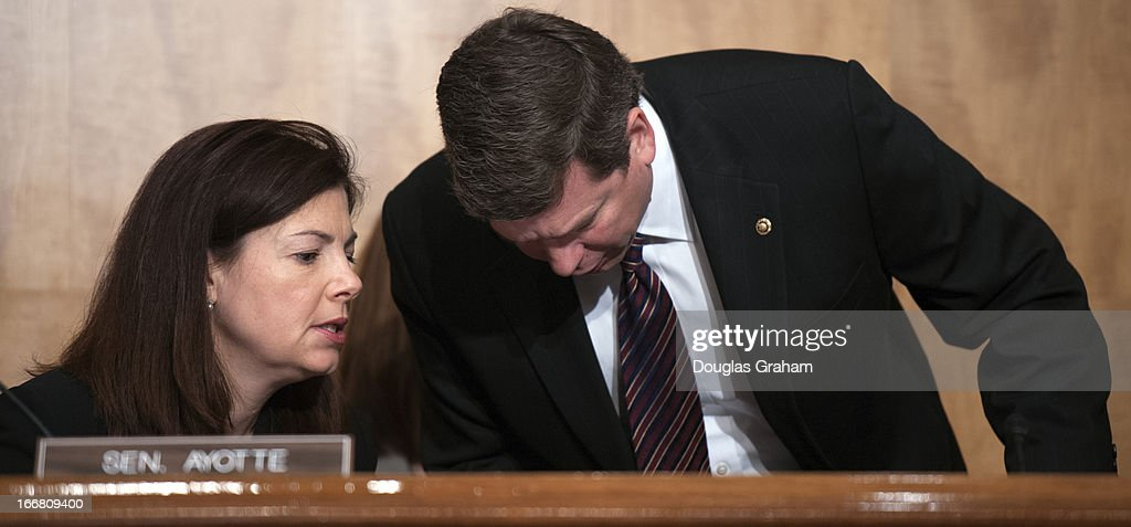 Sen. Kelly Ayotte, R-NH., and Sen. Mark Begich, D-AK., talk during the full committee hearing on the Homeland Security Department's budget submission for FY2014.