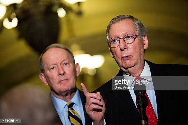 Sen Lamar Alexander looks on as Senate Minority Leader Mitch McConnell speaks during a news conference on Capitol Hill November 21 2013 in Washington...