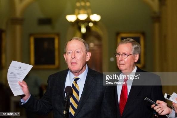 Sen Lamar Alexander speaks as Senate Minority Leader Mitch McConnell looks on during a news conference on Capitol Hill November 21 2013 in Washington...