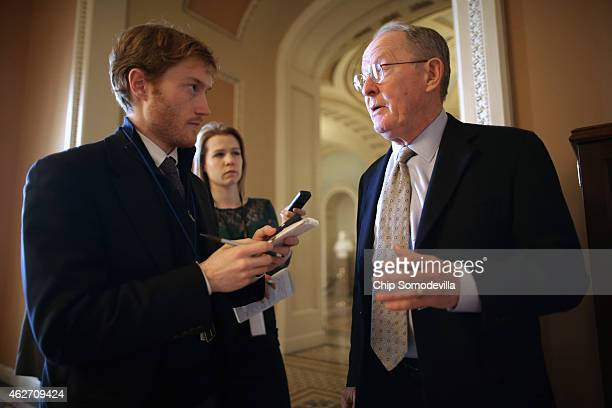 Sen Lamar Alexander talks with reporters before heading into the weekly GOP policy luncheon at the US Capitol February 3 2015 in Washington DC...