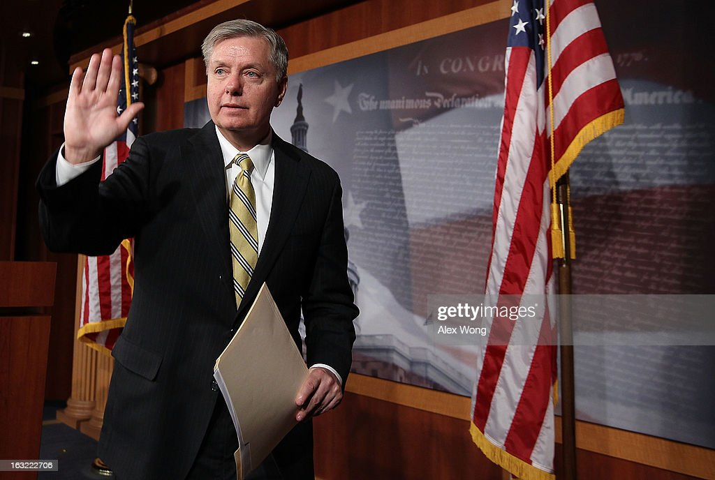 U.S. Sen. <a gi-track='captionPersonalityLinkClicked' href=/galleries/search?phrase=Lindsey+Graham&family=editorial&specificpeople=240214 ng-click='$event.stopPropagation()'>Lindsey Graham</a> (R-SC) waves at the end of a news conference March 6, 2013 on Capitol Hill in Washington, DC. The senators held a news conference on legislation to prevent gun violence.