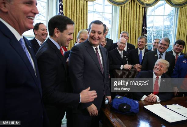 S Sen Marco Rubio and Sen Ted Cruz share a moment as President Donald Trump looks on during a bill signing ceremony in the Oval Office of the White...