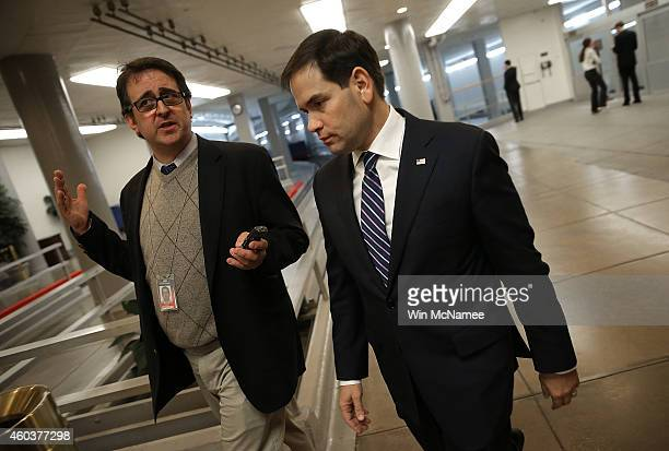 Sen Marco Rubio talks with a reporter as he makes his way to the Senate floor for a series of votes December 12 2014 in Washington DC The US Senate...