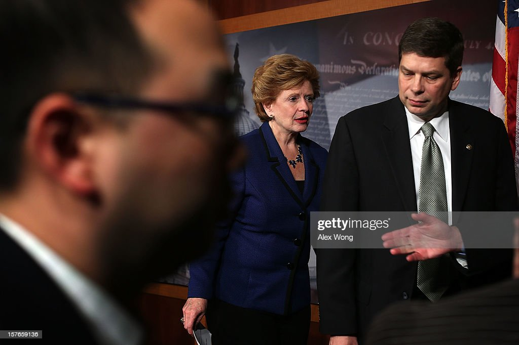 U.S. Sen. <a gi-track='captionPersonalityLinkClicked' href=/galleries/search?phrase=Mark+Begich&family=editorial&specificpeople=5592439 ng-click='$event.stopPropagation()'>Mark Begich</a> (D-AK) (R) and Sen. <a gi-track='captionPersonalityLinkClicked' href=/galleries/search?phrase=Debbie+Stabenow&family=editorial&specificpeople=221624 ng-click='$event.stopPropagation()'>Debbie Stabenow</a> (D-MI) (C) leave after a news conference December 5, 2012 on Capitol Hill in Washington, DC. The senators held a news conference to call on House Republicans to pass the Senate-passed tax cut bill.