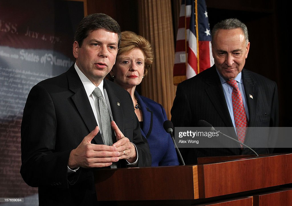 U.S. Sen. Mark Begich (D-AK) speaks as Sen. Debbie Stabenow (D-MI) and Sen. Charles Schumer (D-NY) listen during a news conference December 5, 2012 on Capitol Hill in Washington, DC. The senators held a news conference to call on House Republicans to pass the Senate-passed tax cut bill.