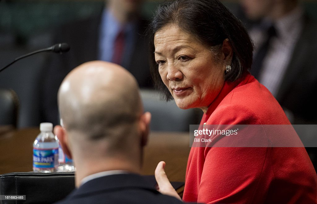Sen. Mazie Hirono, D-Hawaii, speaks with a staff member before the start of the Senate Judiciary Committee mark up hearing on Thursday, Feb. 14, 2013.