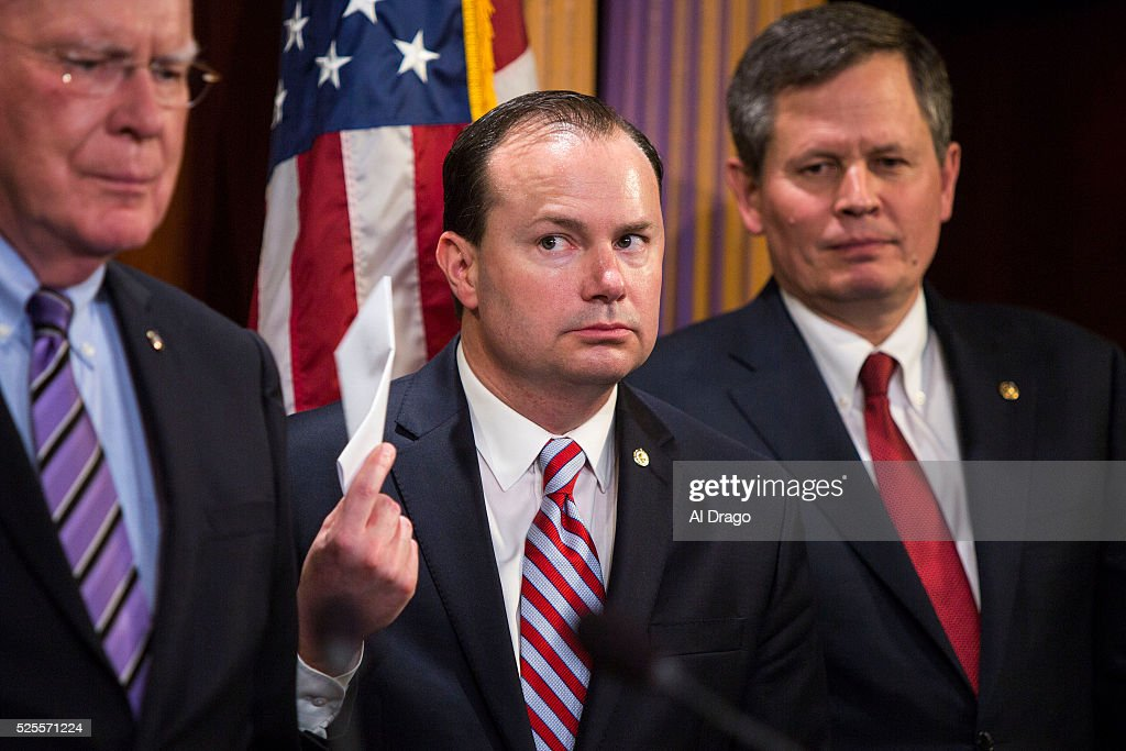 STATES - APRIL 28 - Sen. Mike Lee, R-Utah, fans himself as he listens during a news conference about proposed criminal sentencing reform legislation, in the U.S. Capitol in Washington, Thursday, April 28, 2016. Beside Lee is Sen. Patrick Leahy, D-Vt., left, and Sen. Steve Daines, R-Mont.