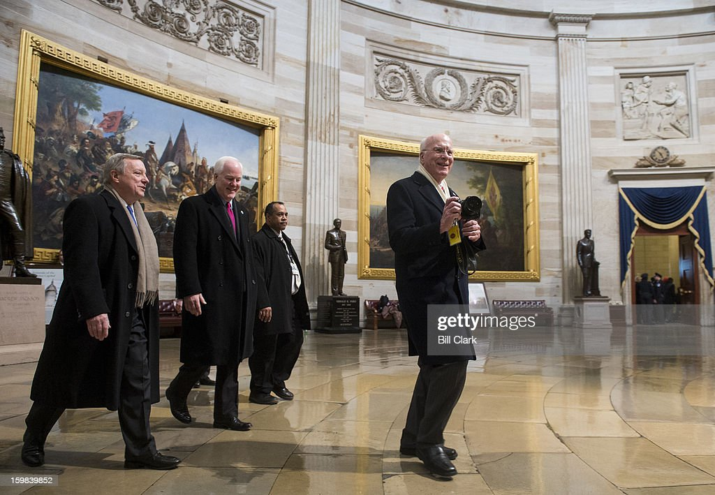 Sen Pat Leahy, D-Vt., right, takes photos of the media camped out in the Rotunda as he leads a procession of Senators, including Sen. Richard Durbin, D-Ill., left, and Sen. John Cornyn, R-Texas, center, to the West Front of the Capitol for President Barack Obama's inauguration ceremony on Monday morning, Jan. 21, 2013.
