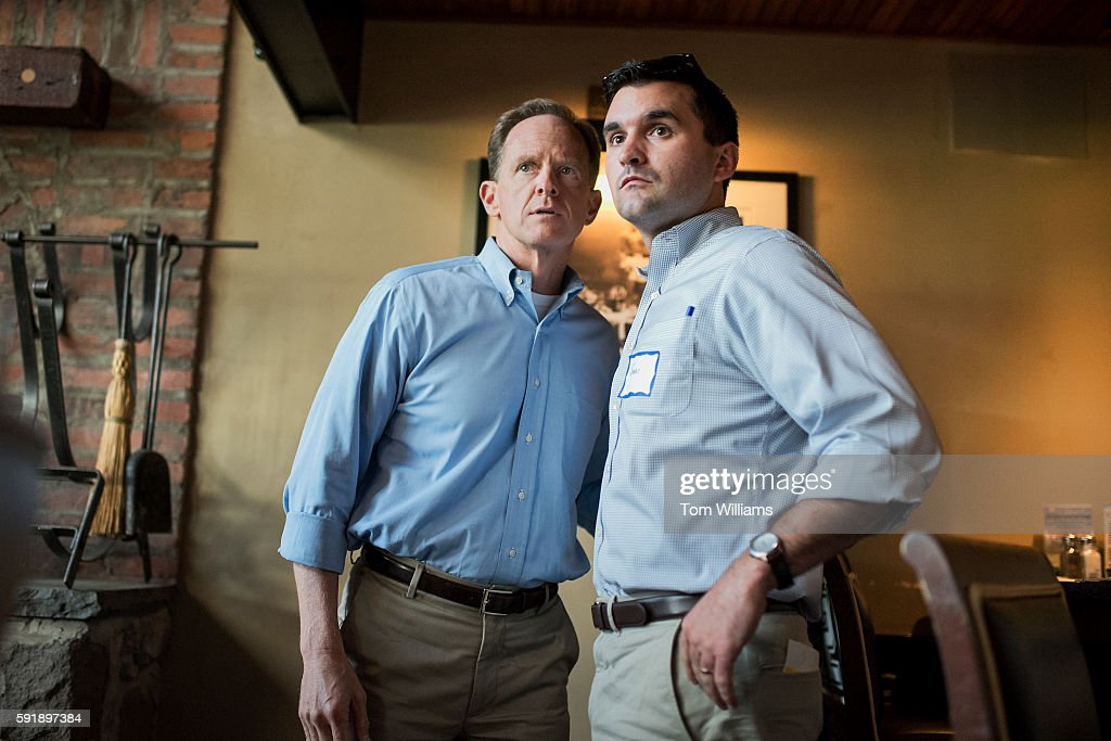 Sen Pat Toomey RPa left talks with aide James Fitzpatrick at Champs Sports Grill in State College Pa during his statewide bus tour August 16 2016
