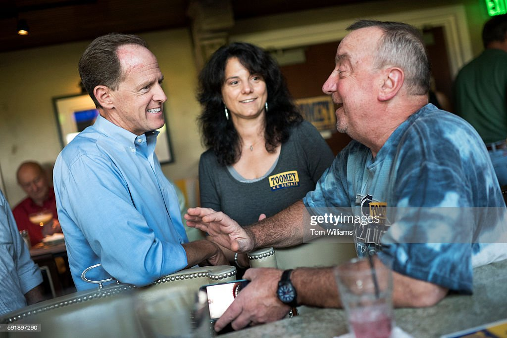 Sen Pat Toomey RPa talks with Tom and Tina Hoy at Champs Sports Grill in State College Pa during his statewide bus tour August 16 2016
