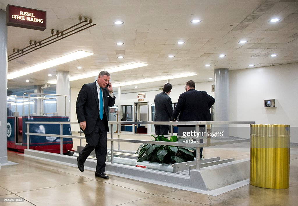 Sen. Richard Burr, R-N.C., talks on his cell phone as he arrives in the Capitol via the Senate subway on Wednesday, Feb. 10, 2016.