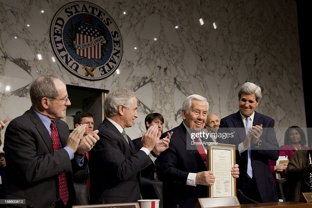 Sen. Richard Lugar (R-IN) (2R) receives applause from (L-R) Sen. James Risch (R-ID), Sen. <a gi-track='captionPersonalityLinkClicked' href=/galleries/search?phrase=Bob+Corker&family=editorial&specificpeople=3986296 ng-click='$event.stopPropagation()'>Bob Corker</a> (R-TN) and Sen. <a gi-track='captionPersonalityLinkClicked' href=/galleries/search?phrase=John+Kerry&family=editorial&specificpeople=154885 ng-click='$event.stopPropagation()'>John Kerry</a> (D-MA) after receiving a service award from his fellow committee members prior to the start of the Senate Foreign Relations Committee hearing on the September 11th attacks on the U.S. Consulate in Benghazi, on Capitol Hill, December 20, 2012 in Washington, DC. Lugar has served in the Senate since 1977.