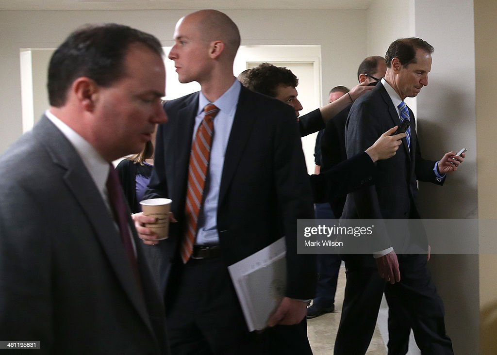 U.S. Sen. <a gi-track='captionPersonalityLinkClicked' href=/galleries/search?phrase=Ron+Wyden&family=editorial&specificpeople=233819 ng-click='$event.stopPropagation()'>Ron Wyden</a> (D-WA) (R) talks to reporters while walking to the Senate chamber to vote on unemployment insurance at the US Capitol January 7, 2014 in Washington, DC. The U.S. Senate voted 60-37 to move forward with a bill to extend federal unemployment benefits for three months.