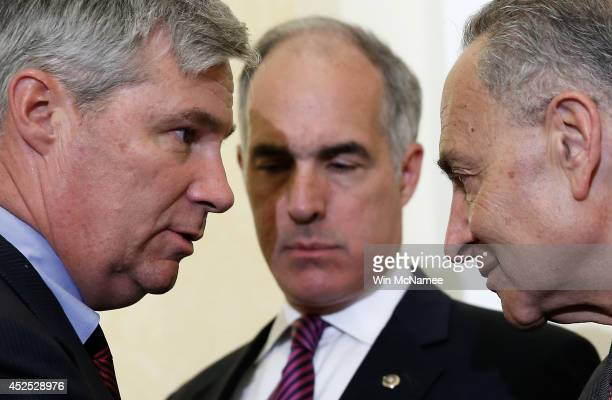 S Sen Sheldon Whitehouse confers with US Sen Charles Schumer as US Sen Robert Casey listens during a press conference about the 'Bring Jobs Home Act'...