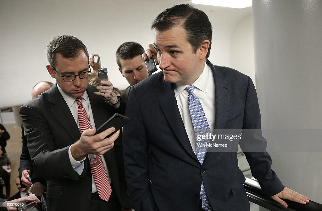 Sen Ted Cruz is trailed by reporters as he makes his way to the Senate floor for a series of votes December 12 2014 in Washington DC The US Senate is...