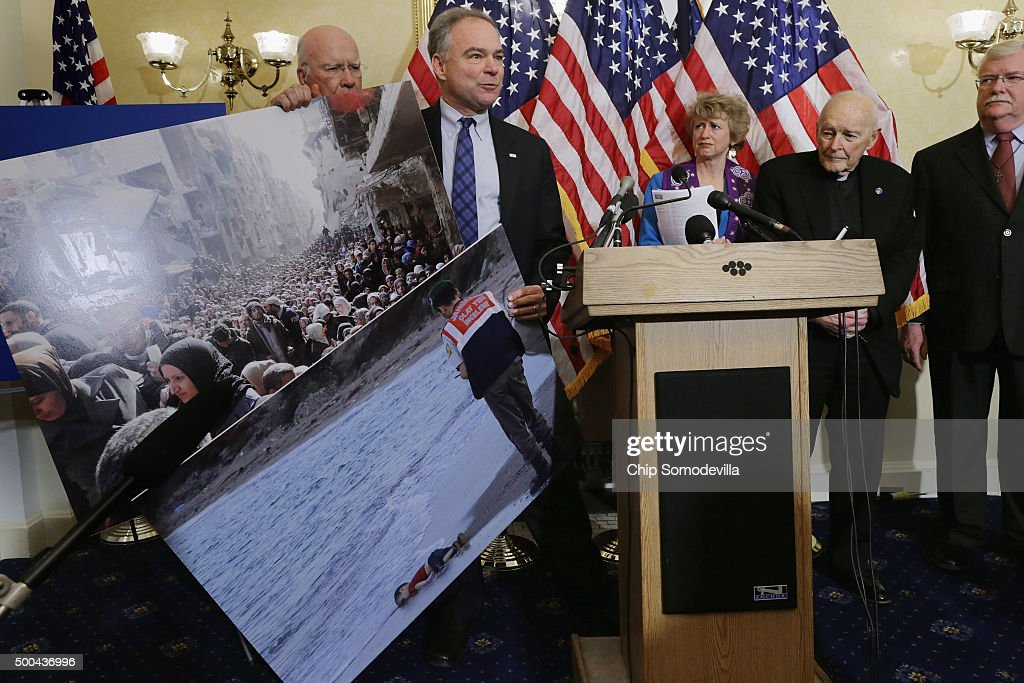 Sen Tim Kaine holds news photographs of Syrians during a news conference with national religious leaders to respond to attempts at vilifying refugees...