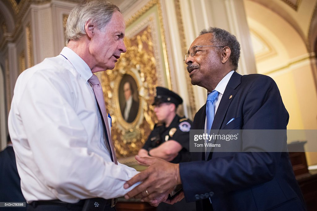 Sen. Tom Carper, D-Del., left, talks with former Sen. Roland Burris, D-Ill., after the Senate Policy luncheons in the Capitol, June 28, 2016.