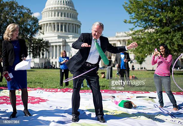 Sen Tom Harkin DIowa hula hoops on top of a giant chutes and ladders game board on the east front of the Capitol during the National Womens Law...