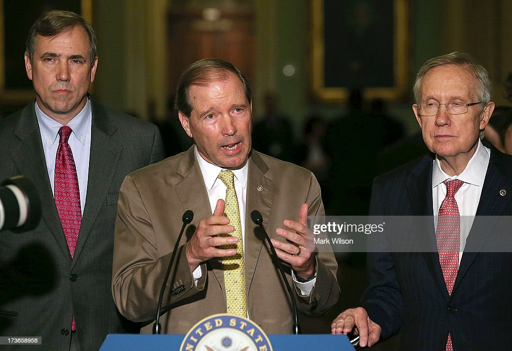 U.S. Sen. Tom Udall (D-CO) (C) speaks to the media while flanked by Senate Majority Leader <a gi-track='captionPersonalityLinkClicked' href=/galleries/search?phrase=Harry+Reid+-+Politician&family=editorial&specificpeople=203136 ng-click='$event.stopPropagation()'>Harry Reid</a> (D-NV) (R), U.S. Sen. <a gi-track='captionPersonalityLinkClicked' href=/galleries/search?phrase=Jeff+Merkley&family=editorial&specificpeople=5507302 ng-click='$event.stopPropagation()'>Jeff Merkley</a> (D-OR), after attending the weekly Senate Democratic policy luncheon at the U.S. Capitol July 16, 2013 in Washington, DC. Democrats gathered a the luncheon to discuss their agenda.