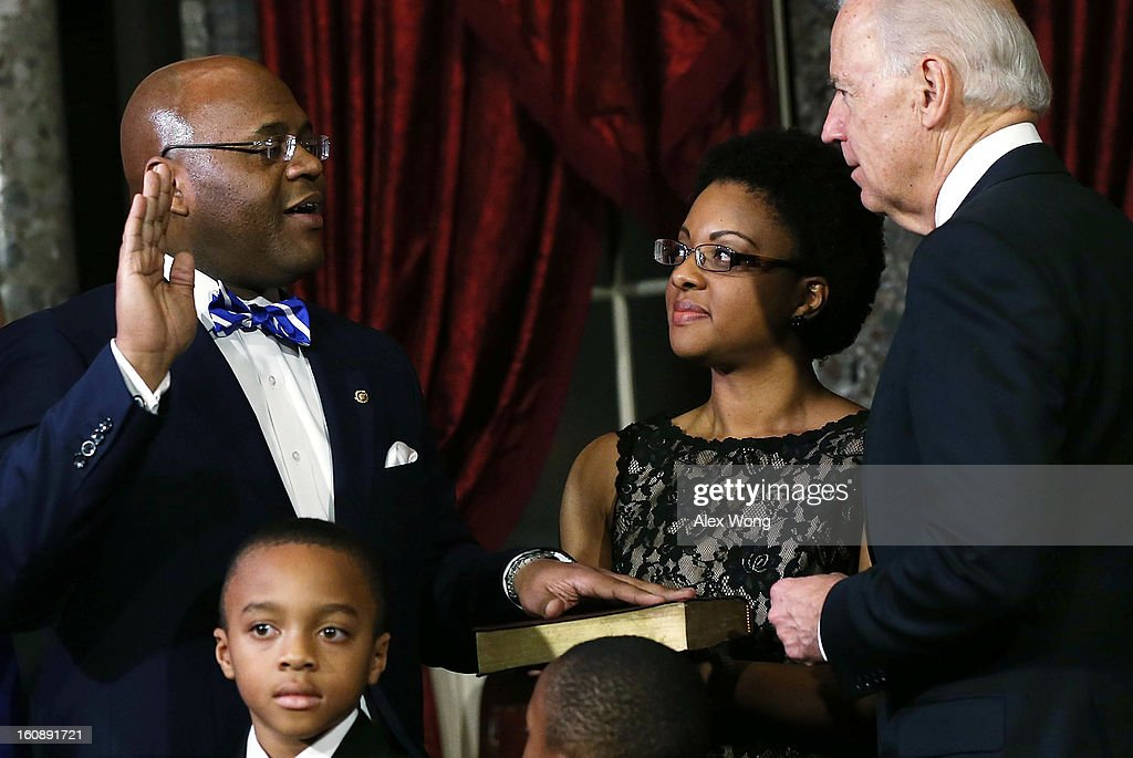 U.S. Sen. William 'Mo' Cowan (D-MA) (L) is sworn in by U.S. Vice President Joseph Biden (R) during a re-enactment of the swearing-in as Cowan's wife Stacy (4th L), sons Miles (2nd L) look on February 7, 2013 at the Old Senate Chamber of the U.S. Capitol in Washington, DC. Cowan was appointed by Massachusetts Governor Deval Patrick as interim U.S. Senator to fill the seat that left vacant by Secretary of State and former U.S. Sen. John Kerry.