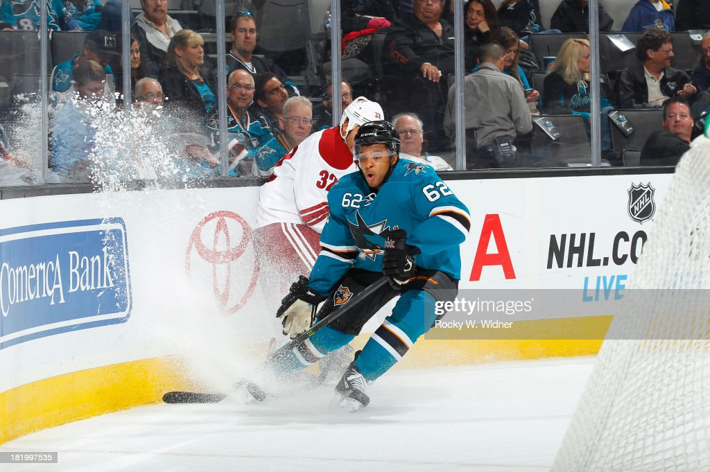Sena Acolatse of the San Jose Sharks skates after the puck against Brandon Yip of the Phoenix Coyotes during a preseason NHL game at SAP Center on...