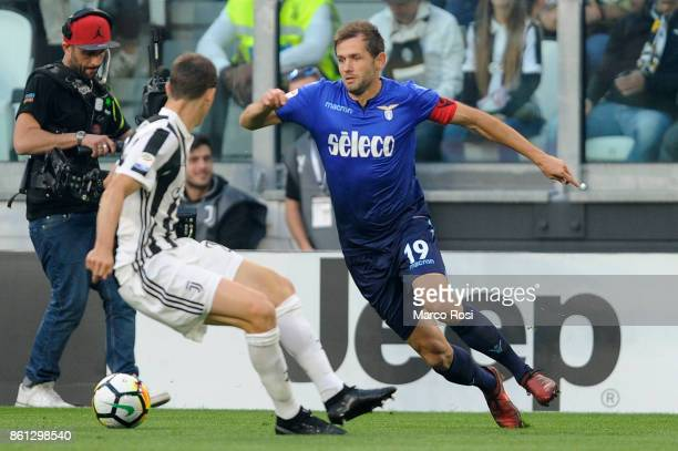 Senad Lulic of SS Lazio compete for the ball with Stephan Lichtsteiner of Juventus during the Serie A match between Juventus and SS Lazio on October...