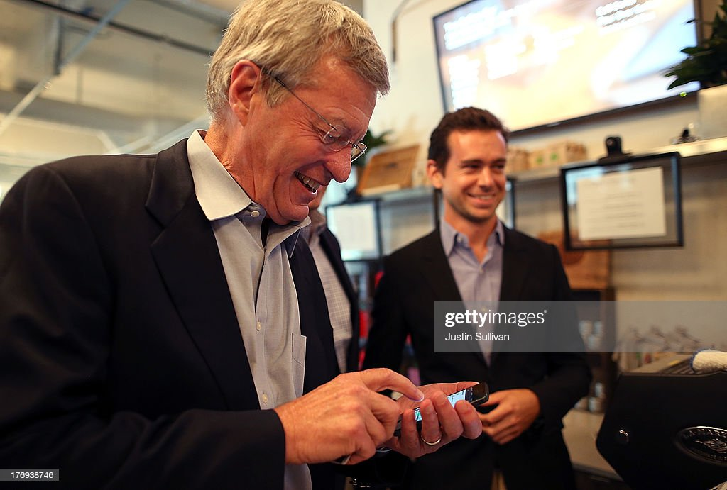 Senate Finance Committee Chairman Max Baucus (D-MT) attempts to download the Square Wallet app while touring the Square headquarters on August 19, 2013 in San Francisco, California. Senators Max Baucus (D-MT) and Dave Camp (R-MI) continued their Tax Reform Tour with a visit to the headquarters of mobile payment company Square. The tour is taking the two senators across the nation to speak to American people about how to fix the nation's broken tax code to benefit families and job creators.