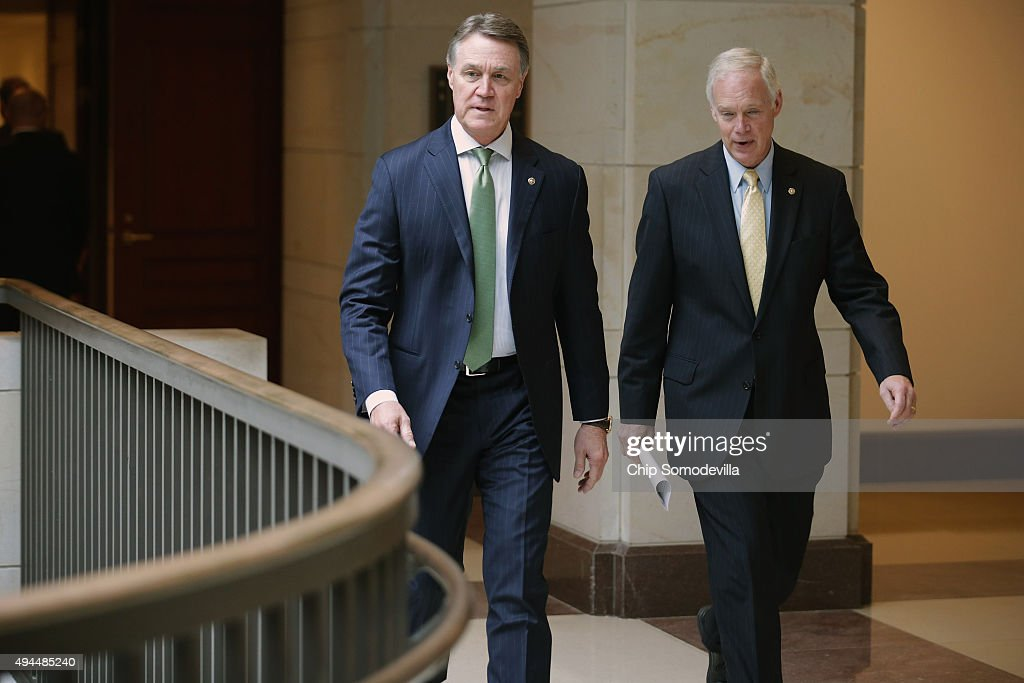 Senate Foreign Relations Committee members Sen. <a gi-track='captionPersonalityLinkClicked' href=/galleries/search?phrase=David+Perdue&family=editorial&specificpeople=4276858 ng-click='$event.stopPropagation()'>David Perdue</a> (R-GA) (L) and Sen. <a gi-track='captionPersonalityLinkClicked' href=/galleries/search?phrase=Ron+Johnson+-+Politiker&family=editorial&specificpeople=12902569 ng-click='$event.stopPropagation()'>Ron Johnson</a> (R-WI) take a quick break from a closed-door heaing with U.S. Secretary of State John Kerry to cast a vote on the Senate floor October 27, 2015 in Washington, DC. Kerry met last week with regional powers, including Saudi Arabia and Turkey, and with his Russian counterpart Sergei Lavrov in an attempt to resolve the four-year-old conflict in Syria.