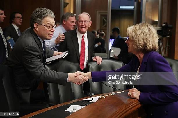 Senate Health Education Labor and Pensions Committee member Sen Al Franken shakes hands with Betsy DeVos Presidentelect Donald Trump's pick to be the...