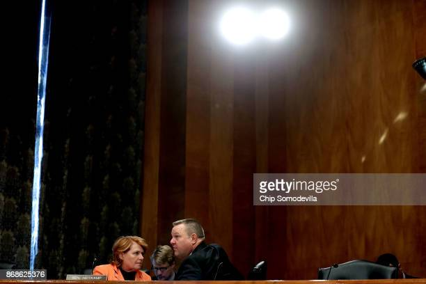 Senate Homeland Security and Governmental Affairs Committee members Sen Heidi Heitkamp and Sen John Tester talk during a hearing in the Dirksen...