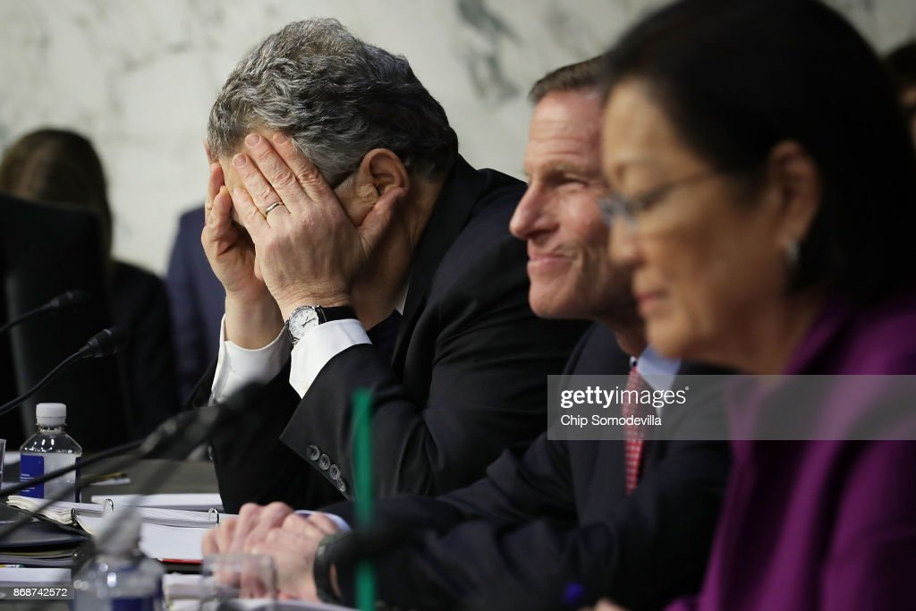 Senate Judiciary Committee member Sen. Al Franken (D-MN) (L) covers his face in frustration as he questions witnesses from Google, Facebook and Twitter during a Crime and Terrorism Subcommittee hearing in the Hart Senate Office Building on Capitol Hill October 31, 2017 in Washington, DC. The committee questioned the tech company representatives about attempts by Russian operatives to spread disinformation and purchase political ads on their platforms, and what efforts the companies plan to use to prevent similar incidents in future elections.