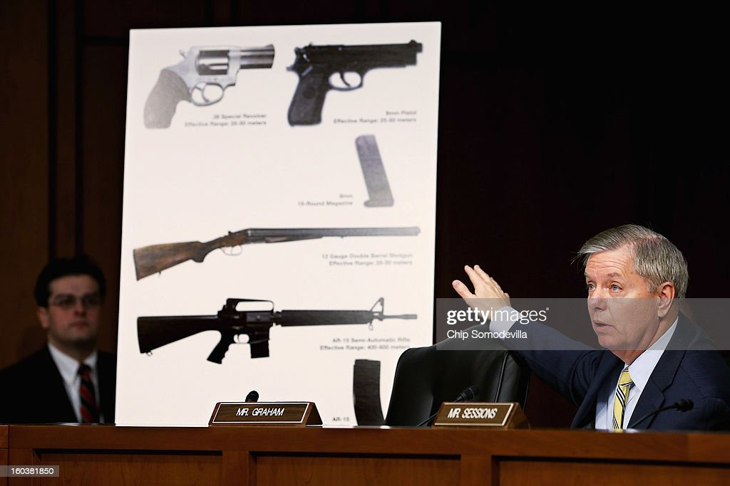 Senate Judiciary Committee member Sen. Lindsey Graham (R-SC) uses imagees of handguns and rifles during a hearing about gun control on Capitol Hill January 30, 2013 in Washington, DC. Shooting victim and former U.S. Rep. Gabby Giffords (D-AZ) delivered an opening statment to the committee, which met for the first time since the mass shooting at a Sandy Hook Elementary School in Newtown, Connecticut.