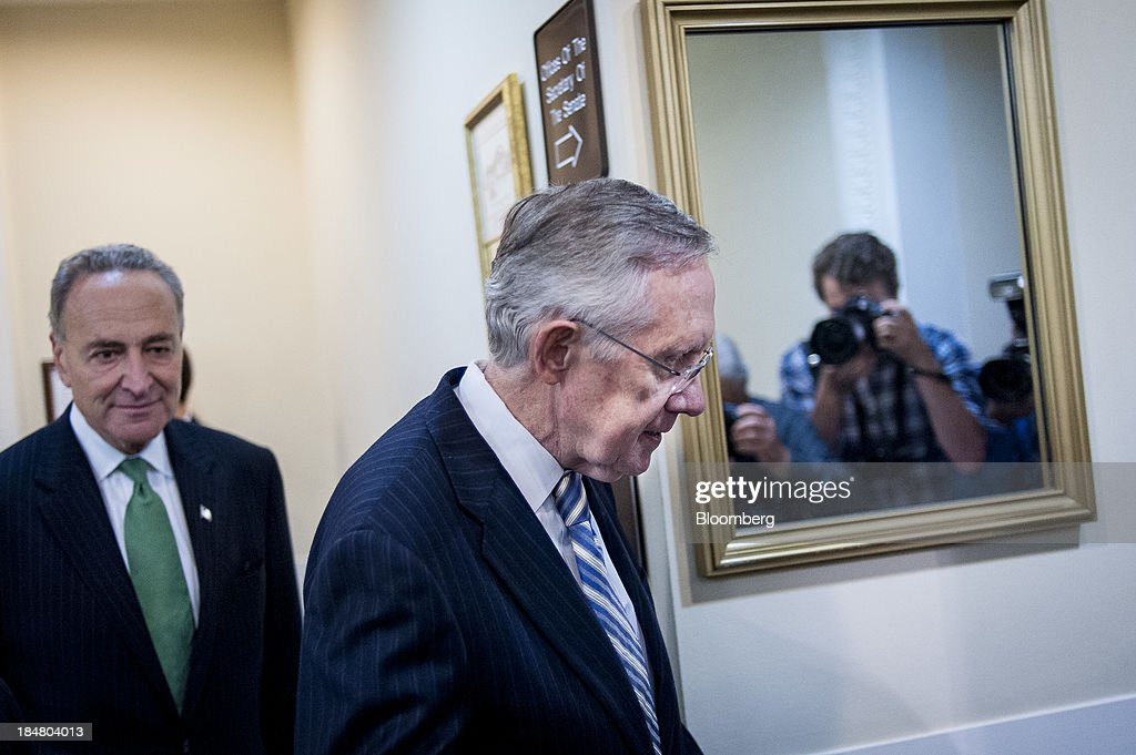 Senate Majority Leader <a gi-track='captionPersonalityLinkClicked' href=/galleries/search?phrase=Harry+Reid+-+Politician&family=editorial&specificpeople=203136 ng-click='$event.stopPropagation()'>Harry Reid</a>, a Democrat from Nevada, center, and Senator <a gi-track='captionPersonalityLinkClicked' href=/galleries/search?phrase=Charles+Schumer&family=editorial&specificpeople=171249 ng-click='$event.stopPropagation()'>Charles Schumer</a>, a Democrat from New York, left, arrive for a news conference as photographers are reflected in a mirror at the U.S. Capitol in Washington, D.C., U.S., on Wednesday, Oct. 16, 2013. The Senate voted 81-18 to halt the 16-day government shutdown and raise the U.S. debt limit, moving one step closer to ending the nation's fiscal impasse. Photographer: Pete Marovich/Bloomberg via Getty Images