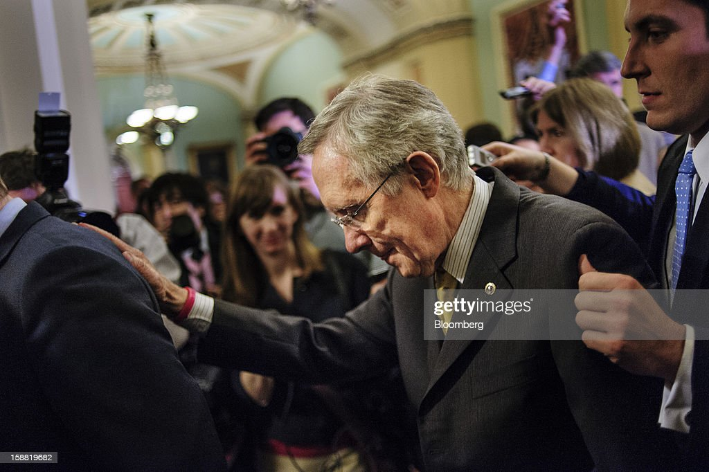Senate Majority Leader <a gi-track='captionPersonalityLinkClicked' href=/galleries/search?phrase=Harry+Reid+-+Pol%C3%ADtico&family=editorial&specificpeople=203136 ng-click='$event.stopPropagation()'>Harry Reid</a>, a Democrat from Nevada, is escorted through a crowd of reporters as he walks to the Senate Floor following a party caucus meeting at the U.S. Capitol in Washington, D.C., U.S., on Sunday, Dec. 30, 2012. Senate Majority Leader <a gi-track='captionPersonalityLinkClicked' href=/galleries/search?phrase=Harry+Reid+-+Pol%C3%ADtico&family=editorial&specificpeople=203136 ng-click='$event.stopPropagation()'>Harry Reid</a> rejected the latest Republican offer to resolve the U.S. fiscal crisis as Minority Leader Mitch McConnell reached out to Vice President Joe Biden in an effort to break the impasse. Photographer: Pete Marovich/Bloomberg via Getty Images