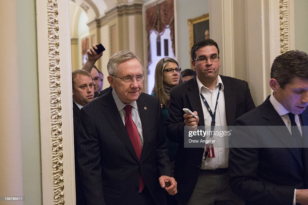 Senate Majority Leader <a gi-track='captionPersonalityLinkClicked' href=/galleries/search?phrase=Harry+Reid+-+Pol%C3%ADtico&family=editorial&specificpeople=203136 ng-click='$event.stopPropagation()'>Harry Reid</a> (D-NV) ignores questions from reporters after meeting with U.S. President Obama and other Congressional leaders at the White House, as he walks to his office on Capitol Hill on December 28, 2012 in Washington, DC. The Senate was back in session on Friday to deal with the looming 'fiscal cliff' issue.