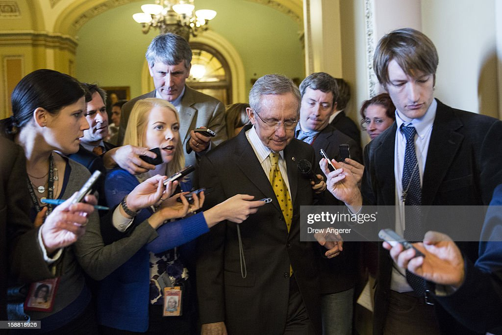 Senate Majority Leader <a gi-track='captionPersonalityLinkClicked' href=/galleries/search?phrase=Harry+Reid&family=editorial&specificpeople=203136 ng-click='$event.stopPropagation()'>Harry Reid</a> (D-NV) (C) leaves the Senate Chamber and heads to a meeting with Senate Democrats on Capitol Hill December 30, 2012 in Washington, DC. The House and Senate are both in session today to deal with the looming 'fiscal cliff.' issue.
