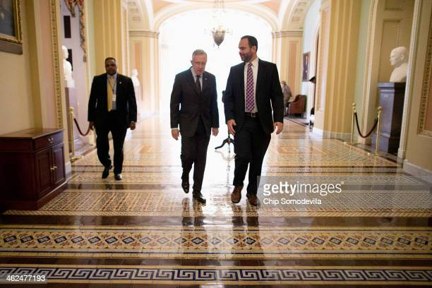 Senate Majority Leader Harry Reid talks with Senior Intelligence and Defense Advisor Tommy Ross as while walking through the US Capitol after opening...