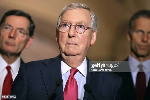 Senate Majority Leader Mitch McConnell talks to reporters with Sen John Barrosso and Sen John Thune following their party's weekly policy luncheon at...