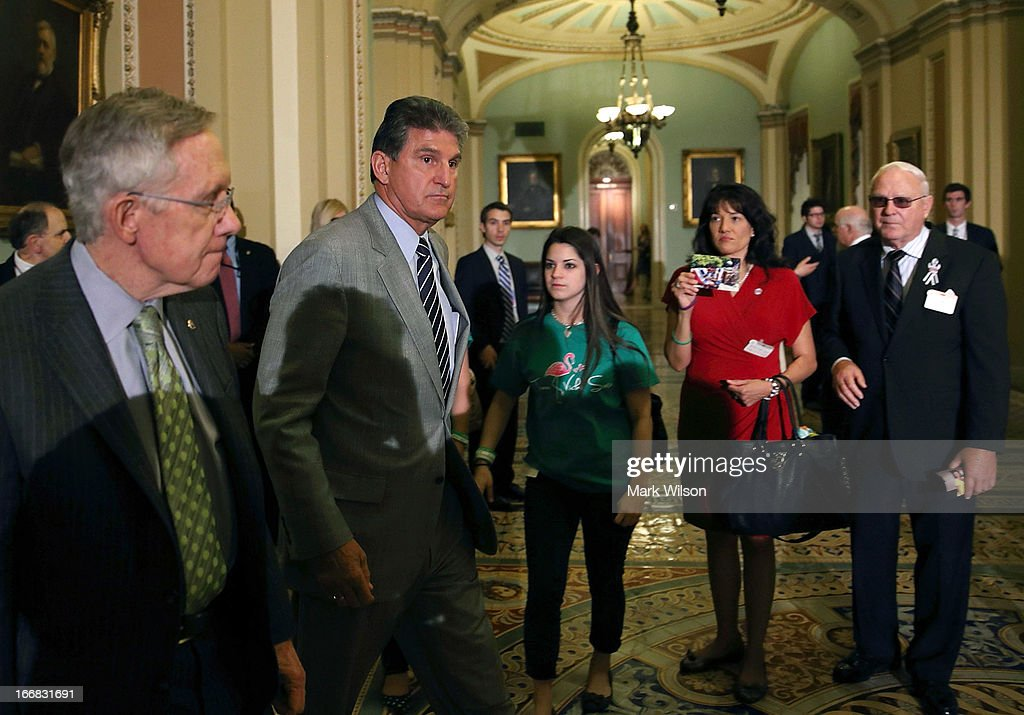 U.S. Senate Majority Leader Sen. <a gi-track='captionPersonalityLinkClicked' href=/galleries/search?phrase=Harry+Reid+-+Politician&family=editorial&specificpeople=203136 ng-click='$event.stopPropagation()'>Harry Reid</a> (D-NV) (L) and Sen. <a gi-track='captionPersonalityLinkClicked' href=/galleries/search?phrase=Joe+Manchin&family=editorial&specificpeople=568465 ng-click='$event.stopPropagation()'>Joe Manchin</a> (D-WV) (2nd L) come out of the Senate Chamber to speak to members of the media as Sandy Hook victim Vicki Soto's sister Carlee Soto (3rd L); Tucson, Arizona shooting victim Christina Taylor Green's mother Roxanna Green (4th L); and Tucson, Arizona, shooting victim Bill Badger (R) look on after a vote on the Senate floor April 17, 2013 on Capitol Hill in Washington, DC. The Senate rejected a proposal by Sens. <a gi-track='captionPersonalityLinkClicked' href=/galleries/search?phrase=Joe+Manchin&family=editorial&specificpeople=568465 ng-click='$event.stopPropagation()'>Joe Manchin</a> (D-WV) and Pat Toomey (R-PA) to expand background checks on firearms purchases and to close the so-called gun-show loophole.