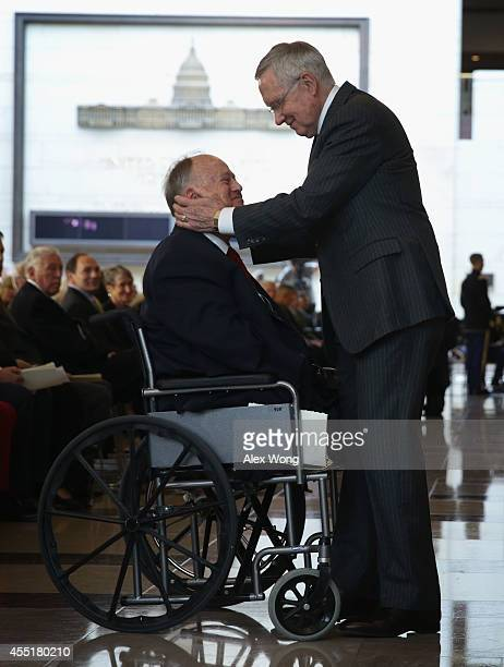 S Senate Majority Leader Sen Harry Reid greets former Sen Max Cleland after a Congressional Gold Medal presentation ceremony at the Emancipation Hall...