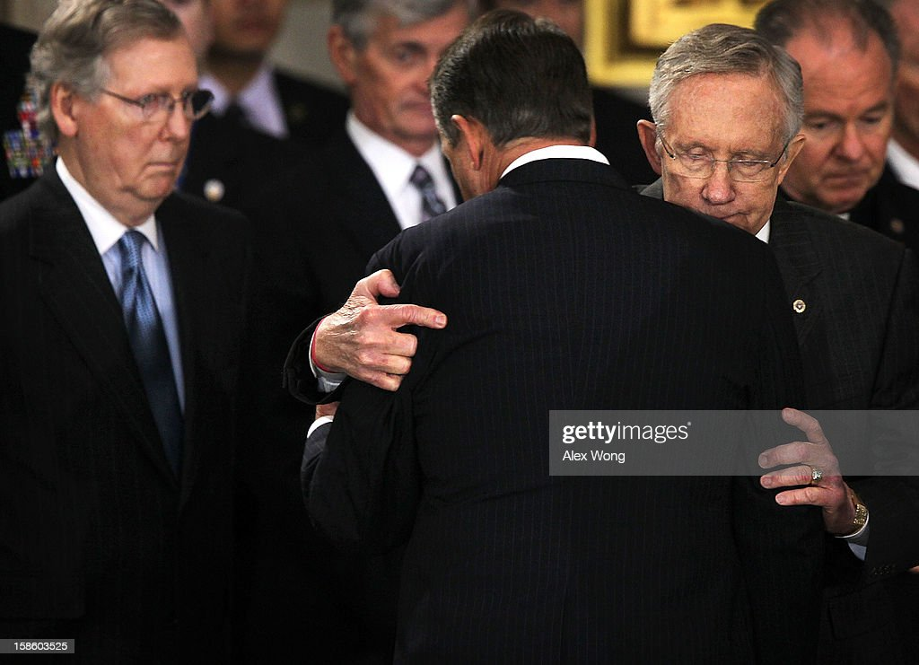 U.S. Senate Majority Leader Sen. <a gi-track='captionPersonalityLinkClicked' href=/galleries/search?phrase=Harry+Reid+-+Politician&family=editorial&specificpeople=203136 ng-click='$event.stopPropagation()'>Harry Reid</a> (D-NV) hugs Speaker of the House Rep. <a gi-track='captionPersonalityLinkClicked' href=/galleries/search?phrase=John+Boehner&family=editorial&specificpeople=274752 ng-click='$event.stopPropagation()'>John Boehner</a> (R-OH) (3rd R) as Senate Minority Leader Sen. <a gi-track='captionPersonalityLinkClicked' href=/galleries/search?phrase=Mitch+McConnell&family=editorial&specificpeople=217985 ng-click='$event.stopPropagation()'>Mitch McConnell</a> (R-KY) (L) looks on as Senator Daniel Inouye (D-HI) lies in state in the Rotunda of the U.S. Capitol during a service December 20, 2012 on Capitol Hill in Washington, DC. The late Senator had died at the age of 88 on Monday at the Walter Reed National Military Medical Center in Bethesda, Maryland where he had been hospitalized since early December. A public funeral service will be held at the Washington National Cathedral on Friday for Senator Inouye, a World War II veteran and the second-longest serving senator in history. His remains will be returned and laid to rest in his home state.