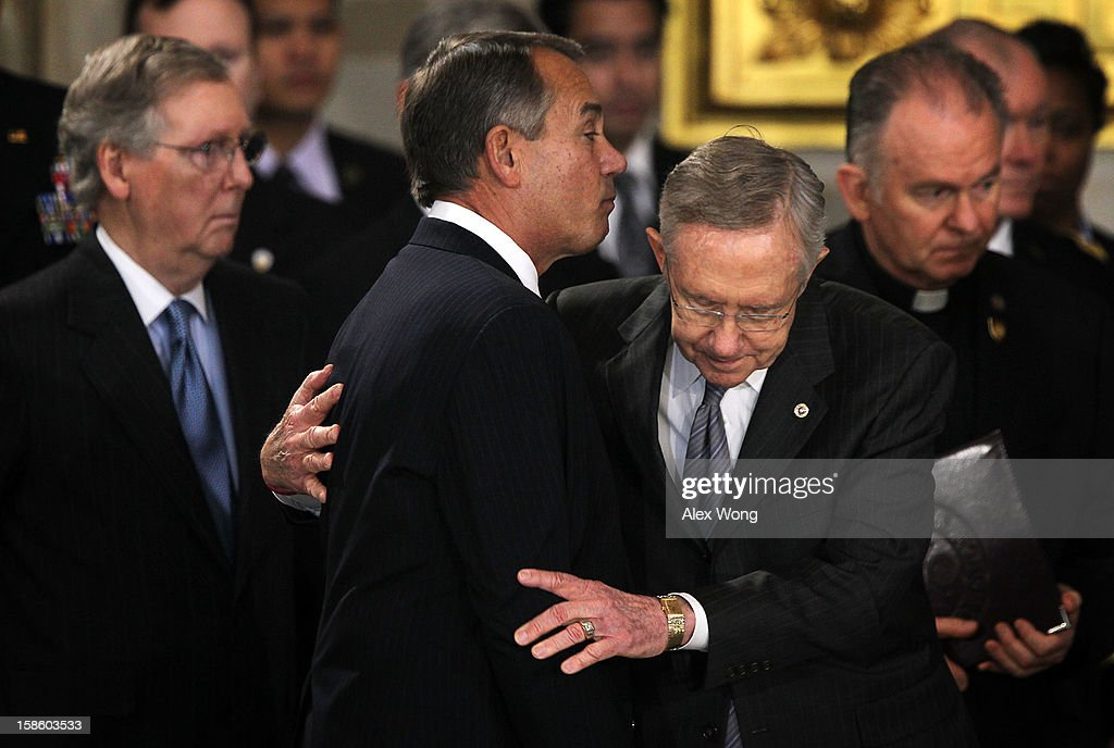 U.S. Senate Majority Leader Sen. <a gi-track='captionPersonalityLinkClicked' href=/galleries/search?phrase=Harry+Reid+-+Politicus&family=editorial&specificpeople=203136 ng-click='$event.stopPropagation()'>Harry Reid</a> (D-NV) hugs Speaker of the House Rep. <a gi-track='captionPersonalityLinkClicked' href=/galleries/search?phrase=John+Boehner&family=editorial&specificpeople=274752 ng-click='$event.stopPropagation()'>John Boehner</a> (R-OH) (3rd R) as Senate Minority Leader Sen. <a gi-track='captionPersonalityLinkClicked' href=/galleries/search?phrase=Mitch+McConnell&family=editorial&specificpeople=217985 ng-click='$event.stopPropagation()'>Mitch McConnell</a> (R-KY) (L) looks on as Senator Daniel Inouye (D-HI) lies in state in the Rotunda of the U.S. Capitol during a service December 20, 2012 on Capitol Hill in Washington, DC. The late Senator had died at the age of 88 on Monday at the Walter Reed National Military Medical Center in Bethesda, Maryland where he had been hospitalized since early December. A public funeral service will be held at the Washington National Cathedral on Friday for Senator Inouye, a World War II veteran and the second-longest serving senator in history. His remains will be returned and laid to rest in his home state.