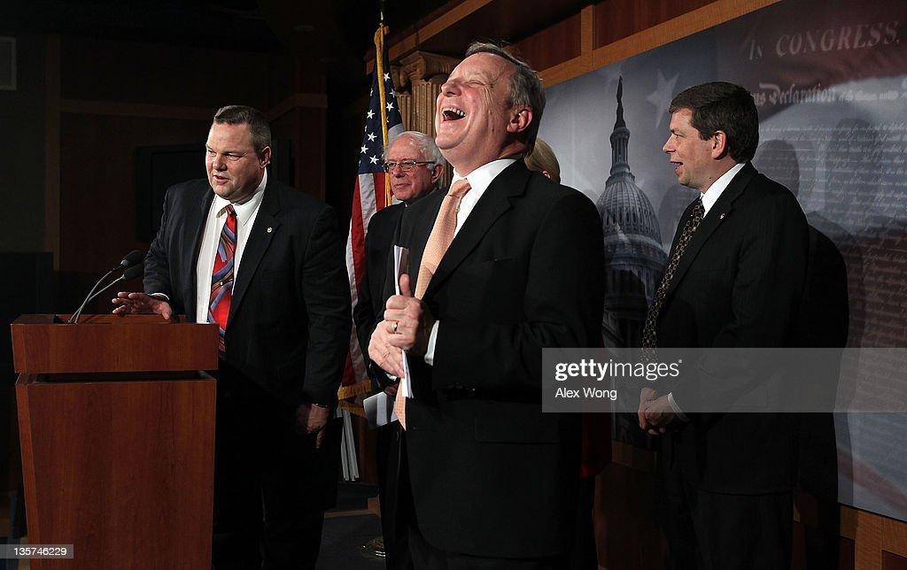 S Senate Majority Whip Sen Richard Durbin reacts as Sen Jon Tester Sen Bernie Sanders and Sen Mark Begich look on during a news conference on...