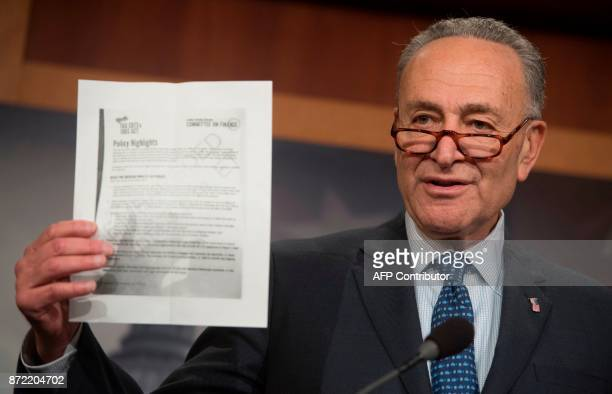 US Senate Minority Leader Chuck Schumer Democrat of New York holds up talking points from the Republican Senate tax reform bill during a press...