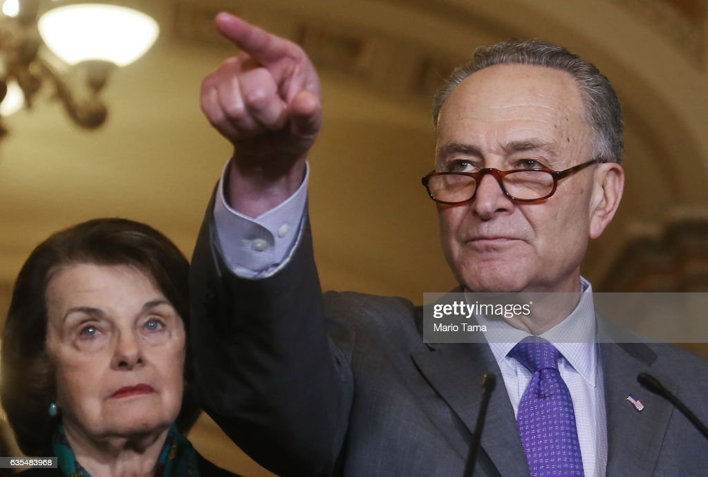 Senate Minority Leader Chuck Schumer (D-NY) points to a reporter as Sen. Dianne Feinstein (D-CA), ranking member of the Senate Judiciary Committee, looks on at a press conference after an emergency Democratic caucus meeting on Capitol Hill on February 15, 2017 in Washington, D.C. Following the resignation of National Security Advisor Michael Flynn, questions about ties between President Trump's team and Russian intelligence agents mounted Wednesday as news of extensive contacts between the two were reported. Democrats and some Republicans are calling for an investigation into Trump's links to Russia.