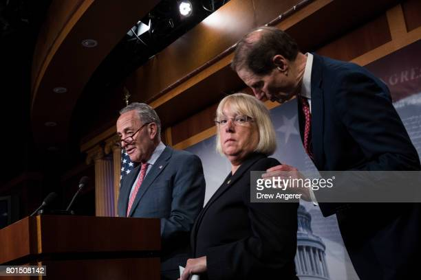 Senate Minority Leader Chuck Schumer speaks as Sen Patty Murray listens to Sen Ron Wyden during a press conference about the Senate Republican health...