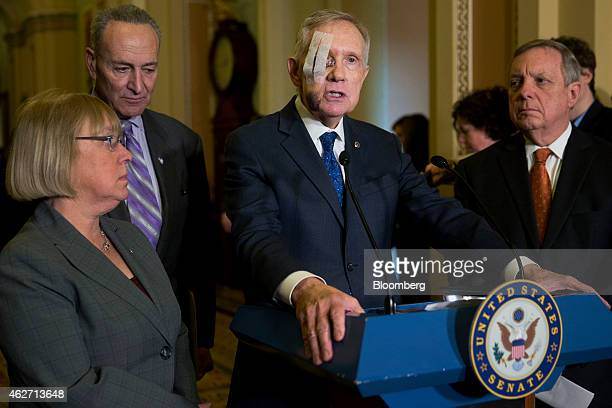 Senate Minority Leader Harry Reid a Democrat from Nevada center speaks with a bandaged eye during a news conference following a Senate luncheon with...