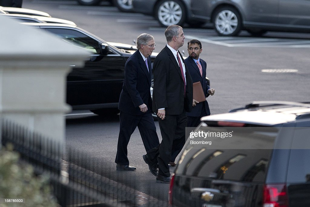 Senate Minority Leader Mitch McConnell, a Republican from Kentucky, left, leaves after a meeting with U.S. President Barack Obama at the White House in Washington, D.C., U.S., on Friday, Dec. 28, 2012. Obama is seeking an up-or-down vote on his proposal to extend tax cuts for annual income up to $250,000, absent a counteroffer from congressional leaders, an official familiar with today's budget talks said. Photographer: Andrew Harrer/Bloomberg via Getty Images