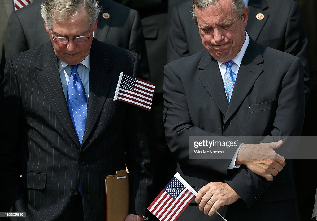 Senate Minority Leader Mitch McConnell (R-KY) and Senate Majority Whip Richard Durbin (D-IL) bow their heads in prayer during a September 11th remembrance ceremony on the steps of the U.S. Capitol September 11, 2013 in Washington, DC. The nation is commemorating the anniversary of the 2001 attacks which resulted in the deaths of nearly 3,000 people after two hijacked planes crashed into the World Trade Center, one into the Pentagon in Arlington, Virginia and one crash landed in Shanksville, Pennsylvania.
