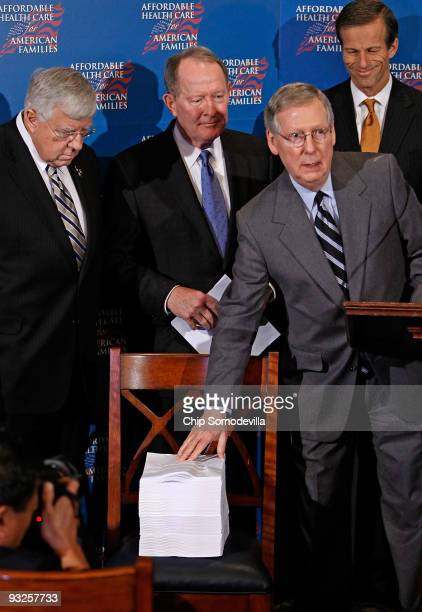 Senate Minority Leader Mitch McConnell points to a copy of the Senate version of health care reform legislation during a news conference with Sen...
